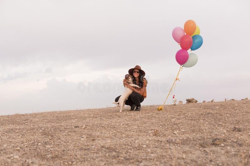 Jonge vrouw die pret met haar hond hebben in openlucht Heliumballons bovendien Zonsondergang Bewolkte hemel royalty-vrije stock foto's