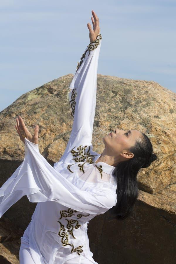 Jonge vrouw die qi gong op een rotsachtig strand van Connecticut uitvoeren stock foto