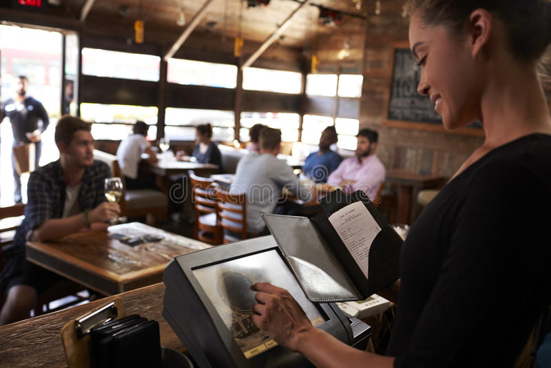 Jonge vrouw die rekening voorbereiden bij restaurant die het aanrakingsscherm met behulp van stock afbeelding