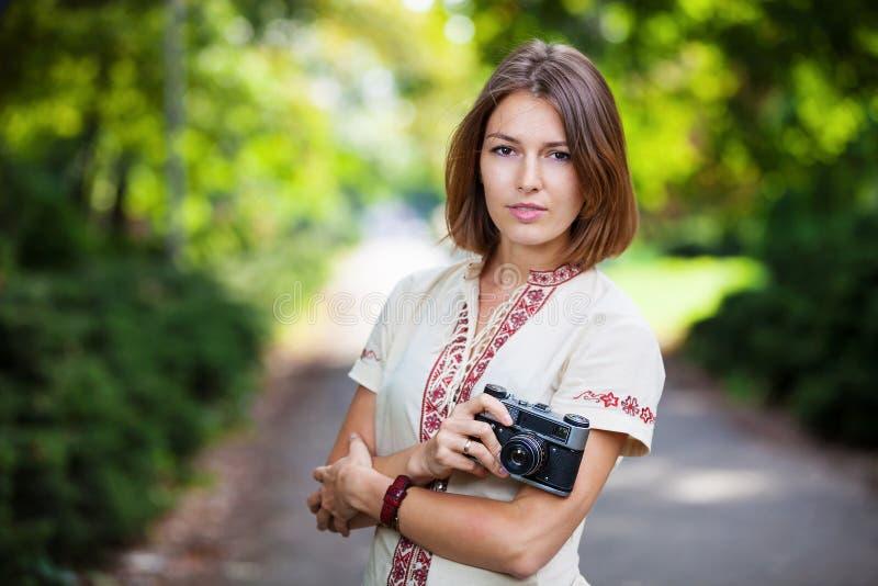 Jonge vrouw die retro stijlcamera in park houden stock foto