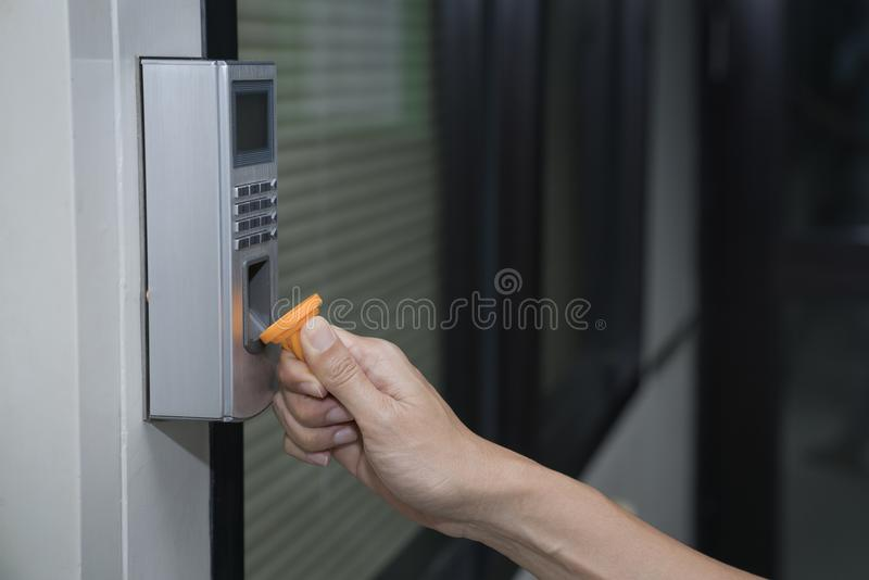 Jonge vrouw die RFID-markeringssleutel gebruiken om de deur te openen royalty-vrije stock foto