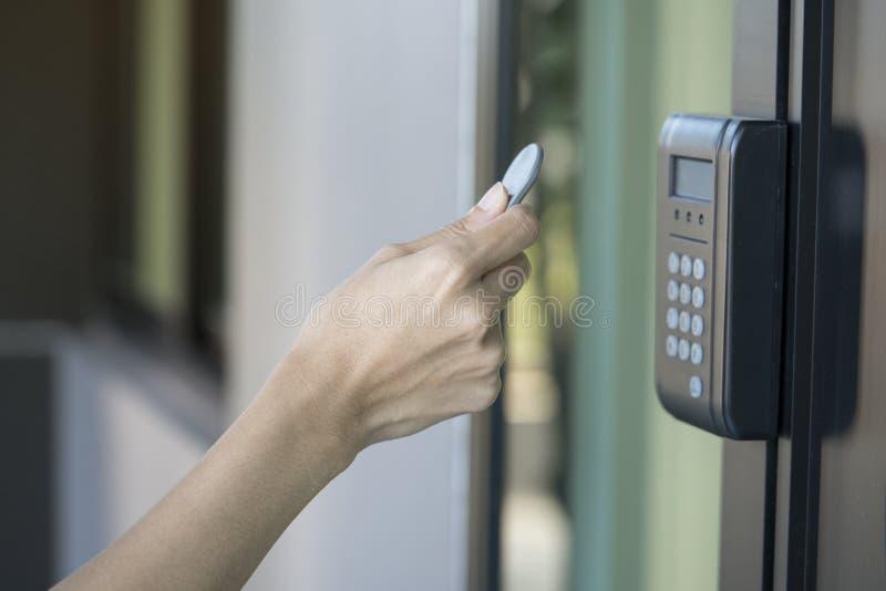 Jonge vrouw die RFID-markeringssleutel gebruiken om de deur te openen stock afbeeldingen