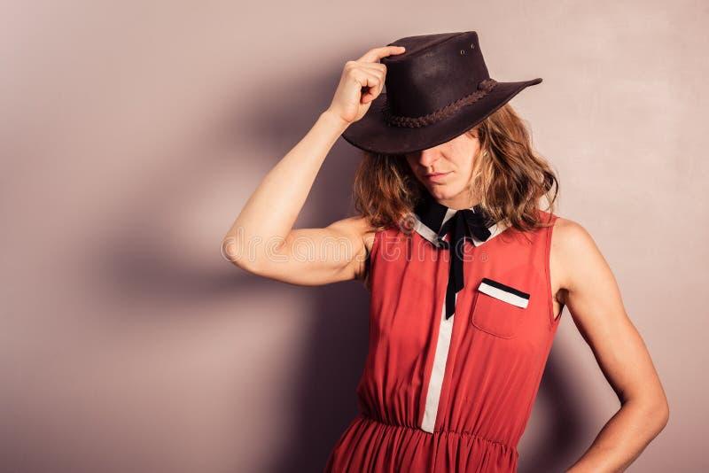 Jonge vrouw die rode kleding en cowboyhoed dragen royalty-vrije stock afbeelding