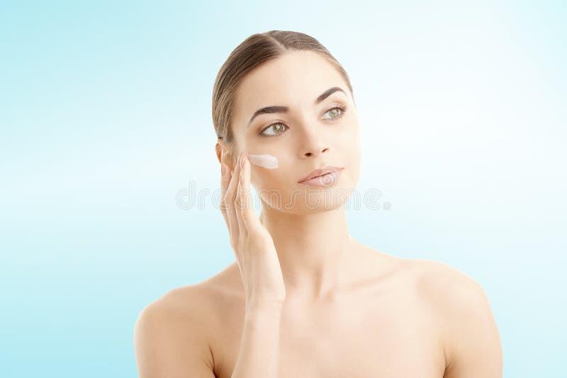 Jonge vrouw die room op haar gezicht toepassen stock afbeeldingen