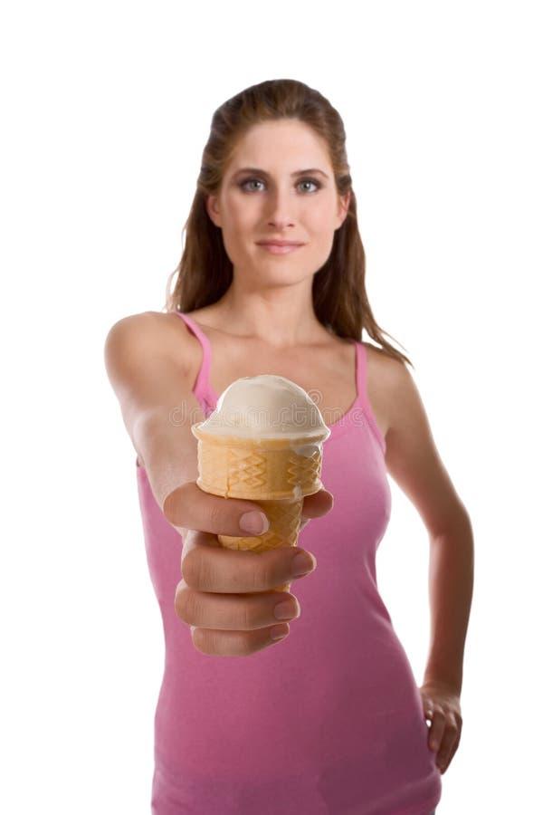 Jonge vrouw die roomijs in wafelkegel aanbiedt stock afbeelding