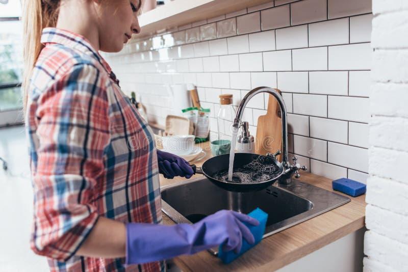 Jonge vrouw die rubberhandschoenen dragen die pan in keuken wassen royalty-vrije stock afbeelding