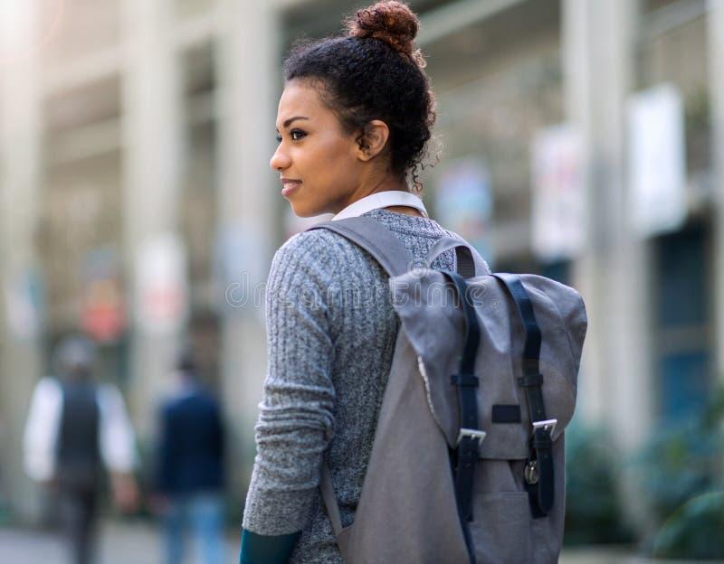 Jonge vrouw die rugzak in stad dragen stock foto