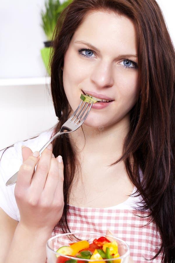 Jonge vrouw die salade eet stock foto's