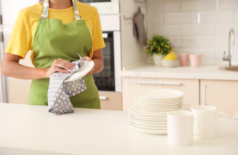 Jonge vrouw die schone plaat in keuken afvegen stock foto
