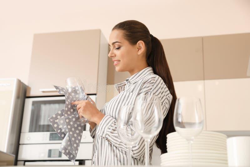 Jonge vrouw die schoon glas in keuken afvegen stock fotografie