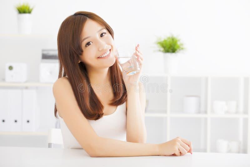 Jonge vrouw die schoon water drinken stock afbeeldingen