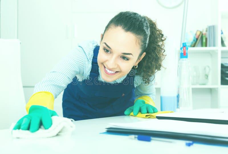 Jonge vrouw die schoonmaak in modern bureau doen stock afbeelding