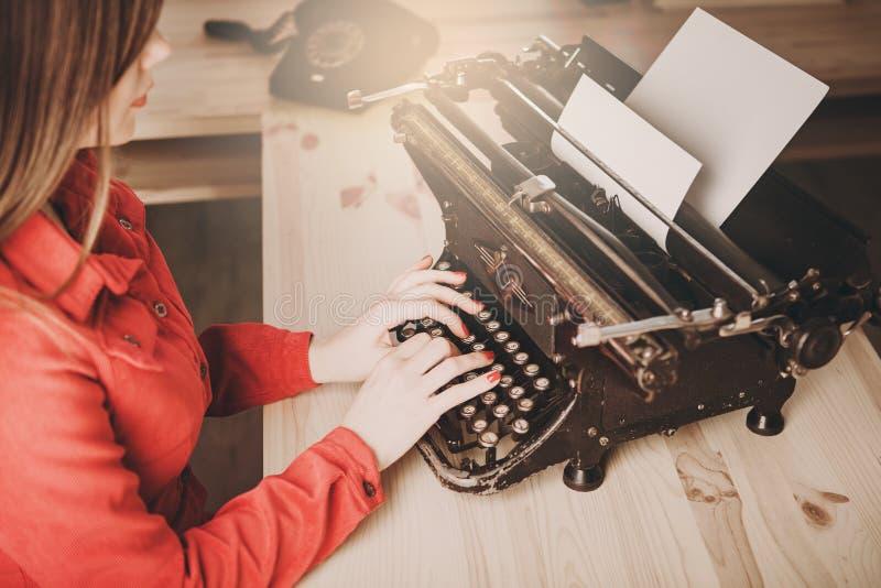 Jonge vrouw die schrijfmachine, bedrijfsconcepten, retro beeld s met behulp van stock afbeelding