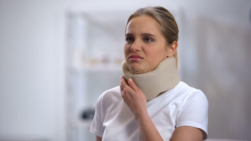 Jonge vrouw die in schuim cervicale kraag scherpe pijn in hals voelen, traumaresultaat stock foto