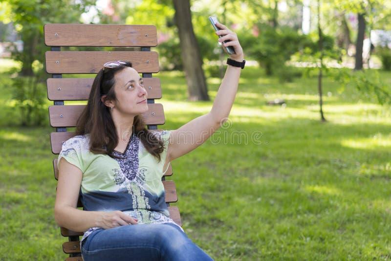 Jonge vrouw die selfie in het park maken Sexy jonge vrouw met lang blond haar die selfie op de zomerdag doen in park Vrolijk meis stock fotografie