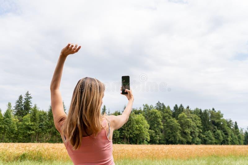 Jonge vrouw die selfie met haar mobiele buiten telefoon maken royalty-vrije stock foto's