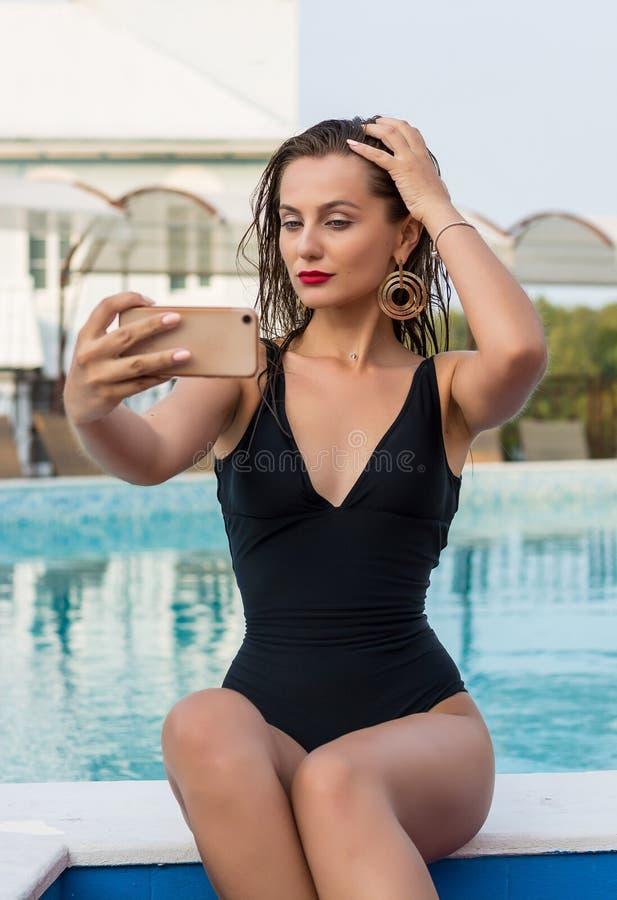 Jonge vrouw die selfie op een smartphone in de pool doen royalty-vrije stock fotografie