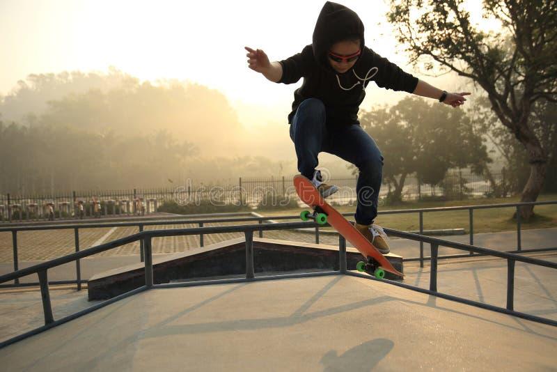 Jonge vrouw die skateboarder bij skatepark met een skateboard rijden stock fotografie