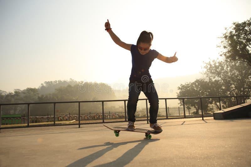 Jonge vrouw die skateboarder bij skatepark met een skateboard rijden stock foto