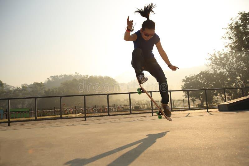 Jonge vrouw die skateboarder bij skatepark met een skateboard rijden stock afbeeldingen