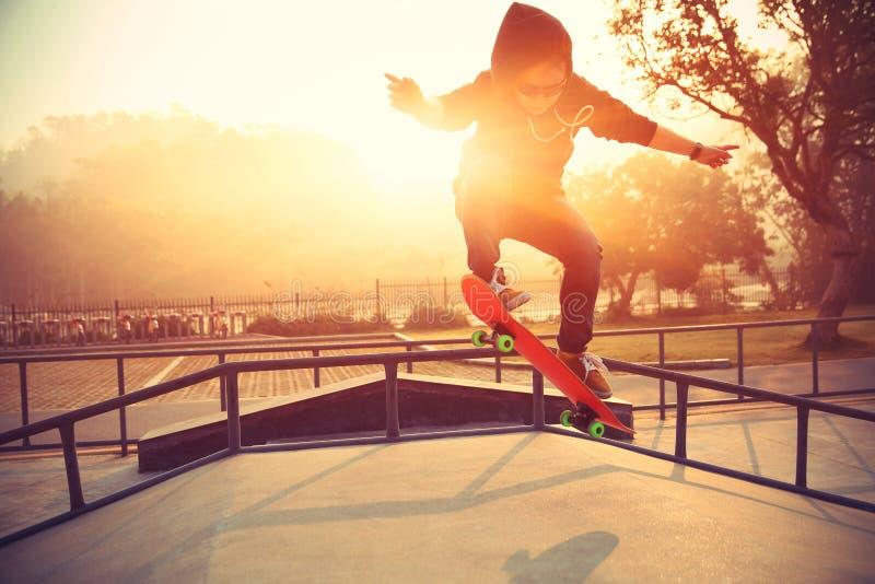Jonge vrouw die skateboarder bij skatepark met een skateboard rijden royalty-vrije stock afbeelding