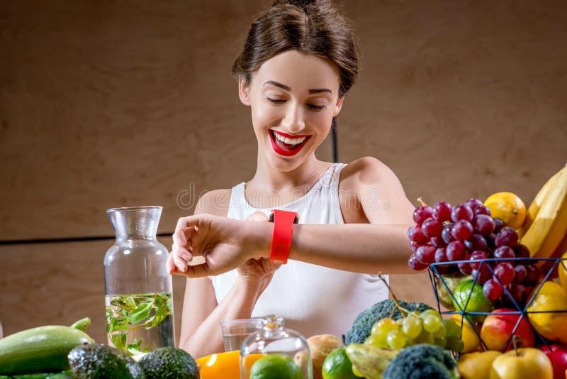 Jonge vrouw die slim horloge in de keuken met behulp van stock afbeelding