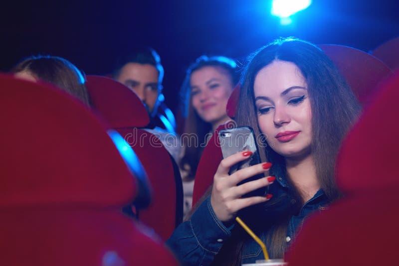 Jonge vrouw die slimme telefoon met behulp van bij de bioskoop stock afbeeldingen