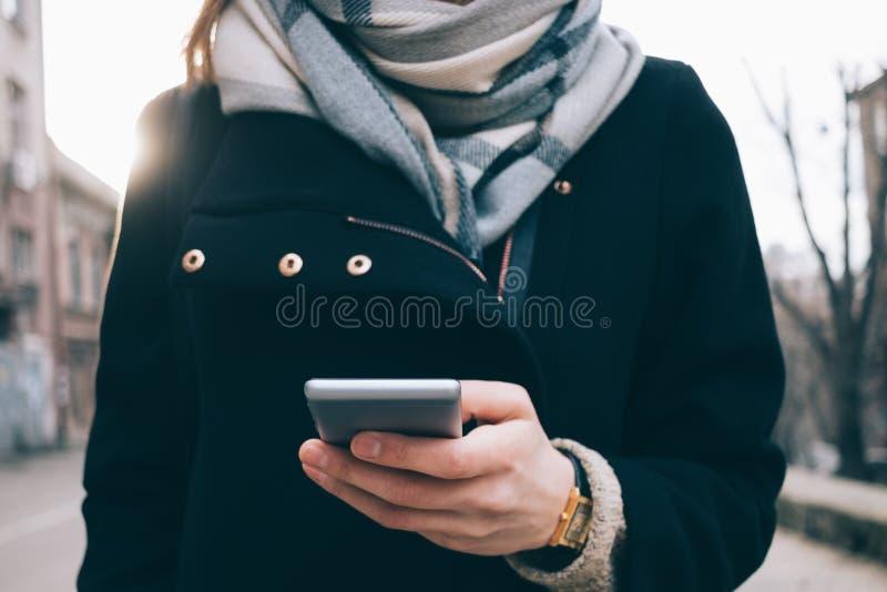 Jonge vrouw die slimme telefoon in openlucht met behulp van royalty-vrije stock afbeelding