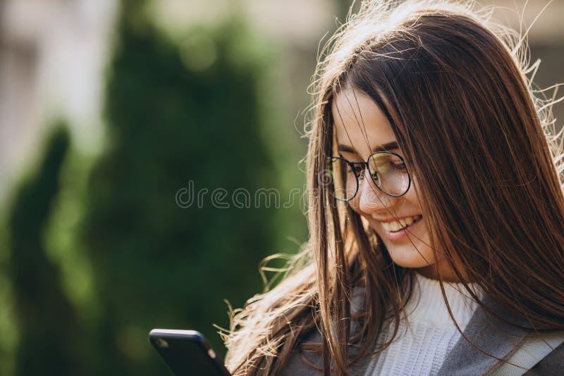 Jonge vrouw die of smartphone texting gebruiken stock foto