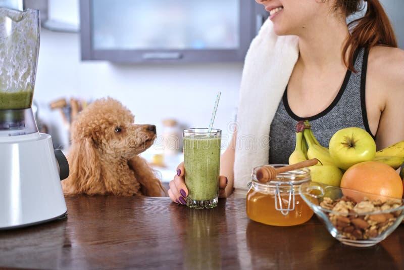Jonge vrouw die smoothie in huiskeuken drinken stock foto's