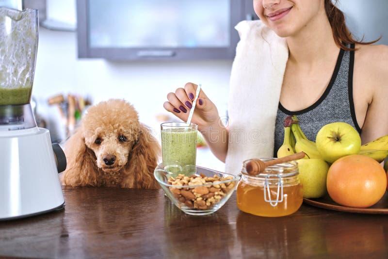 Jonge vrouw die smoothie in huiskeuken drinken royalty-vrije stock afbeelding