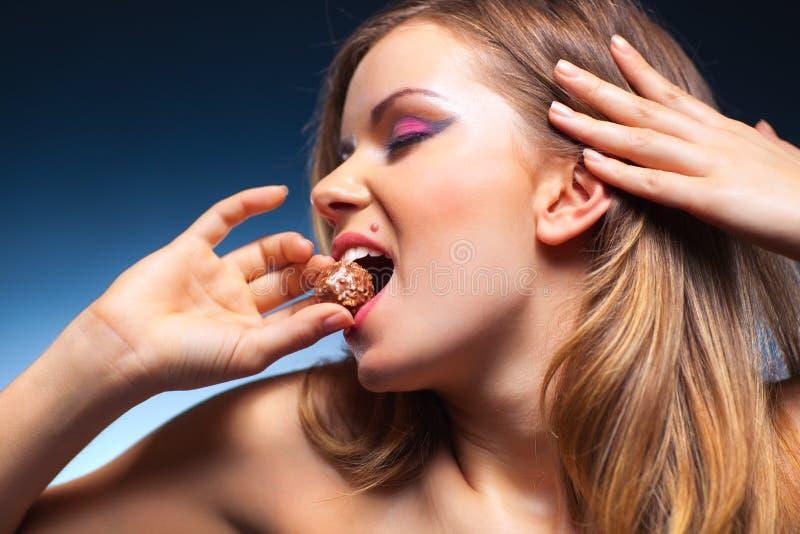 Jonge vrouw die snoepje eet stock foto's