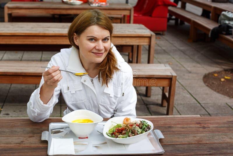 Jonge vrouw die soep en salade in openluchtrestaurant eten. royalty-vrije stock fotografie