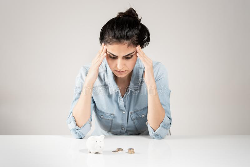 Jonge vrouw die spaarvarken kijken die met hand wordt beklemtoond op hoofd royalty-vrije stock foto's