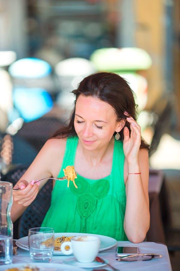 Jonge vrouw die spaghetti eten bij openluchtkoffie op Italiaanse vakantie stock afbeelding