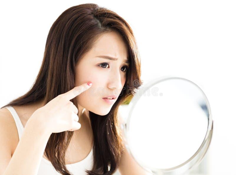 Jonge vrouw die spiegel onderzoekt stock fotografie