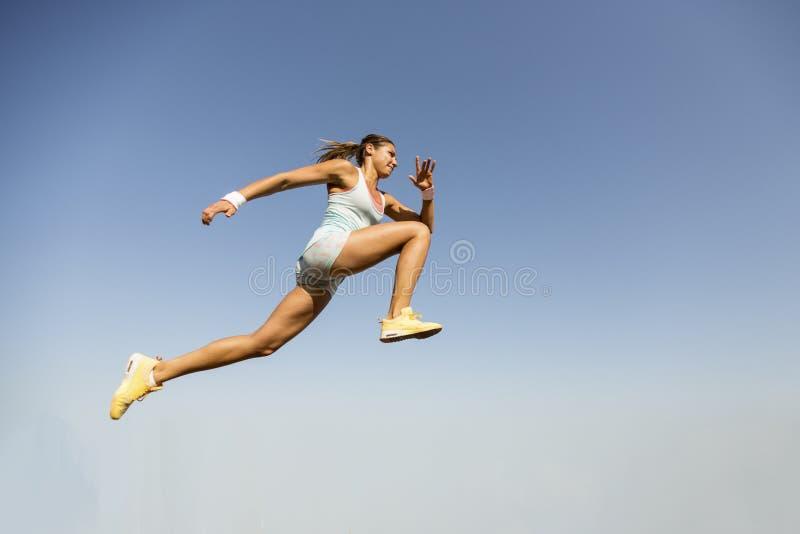 Jonge vrouw die sprong lang duren royalty-vrije stock afbeeldingen