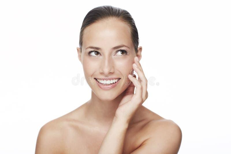 Jonge vrouw die in studio glimlacht stock foto