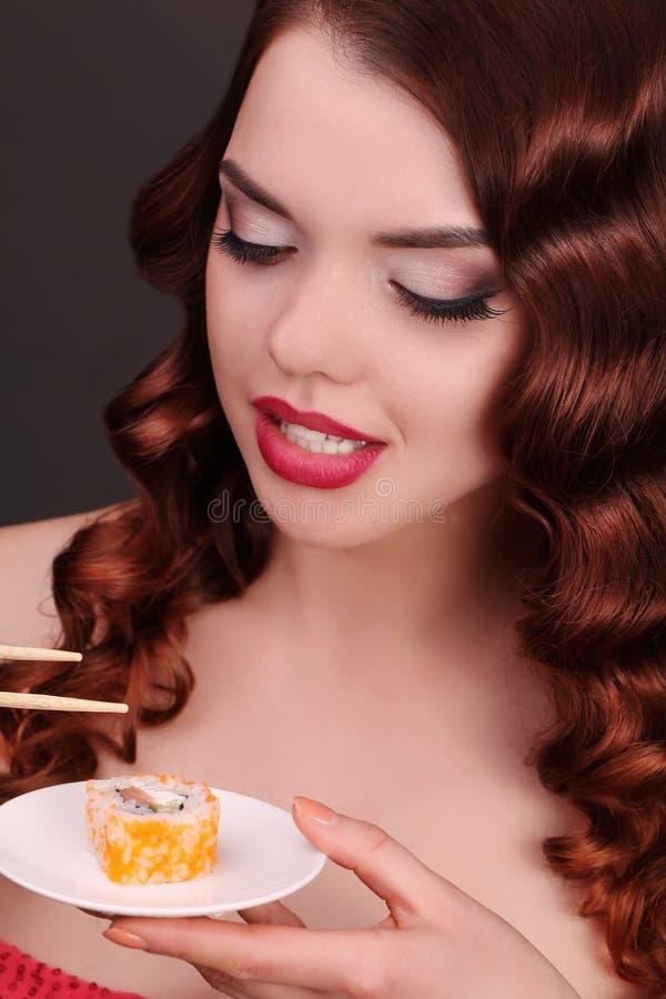 Jonge vrouw die sushi met eet eetstokjes royalty-vrije stock afbeeldingen
