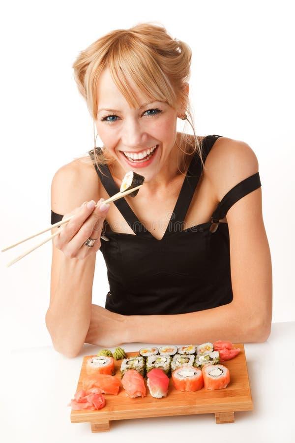 Jonge vrouw die sushi met eetstokjes eet royalty-vrije stock fotografie