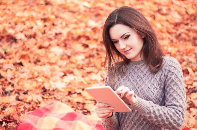Jonge vrouw die tablet in een park gebruiken royalty-vrije stock fotografie