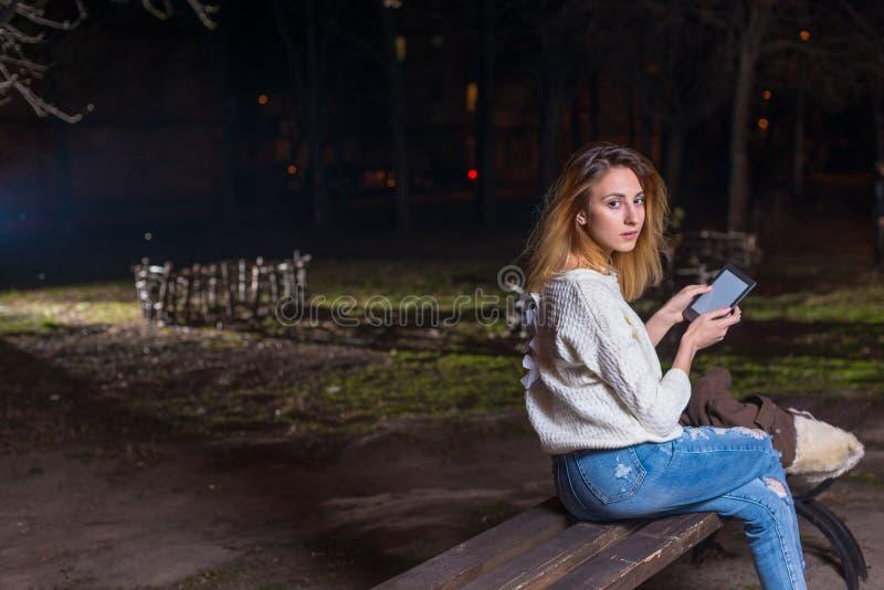 Jonge vrouw die tablet het openlucht glimlachen gebruiken stock afbeeldingen