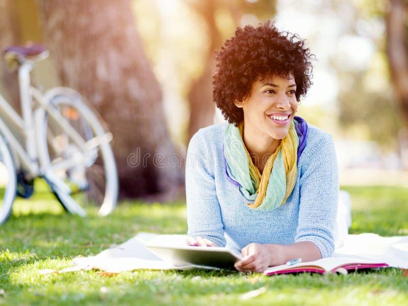 Jonge vrouw die tablet in het park gebruiken stock afbeelding