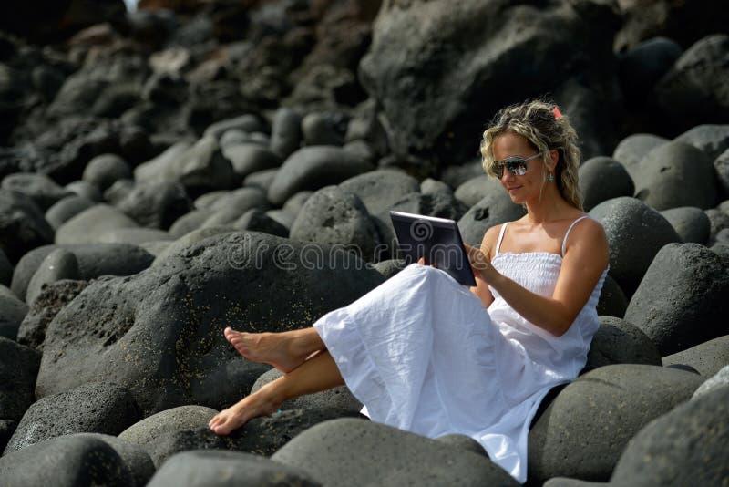Jonge vrouw die tablet op rotsachtig strand gebruikt stock afbeelding