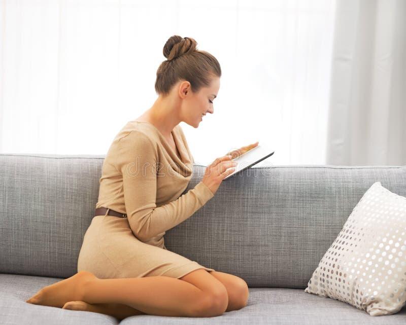 Jonge vrouw die tabletpc met behulp van terwijl het zitten op bank stock foto's