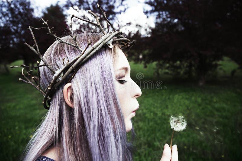 Jonge vrouw die takjekroon dragen en op paardebloem blazen stock afbeeldingen