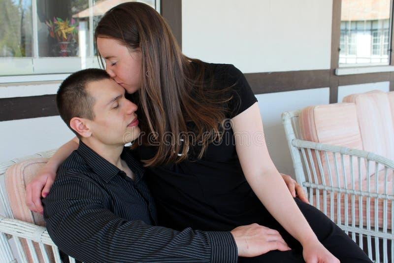 Jonge vrouw die teder het voorhoofd van haar minnaar kussen stock foto
