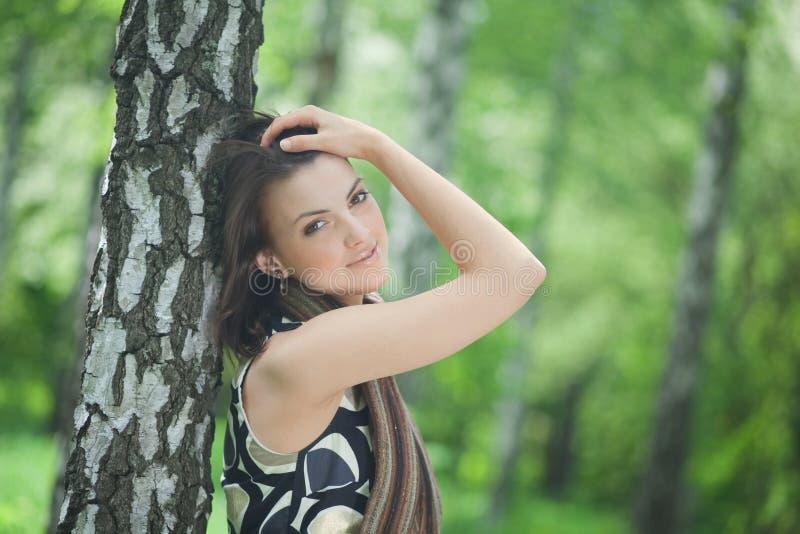 Jonge vrouw die tegen een boom leunt stock foto
