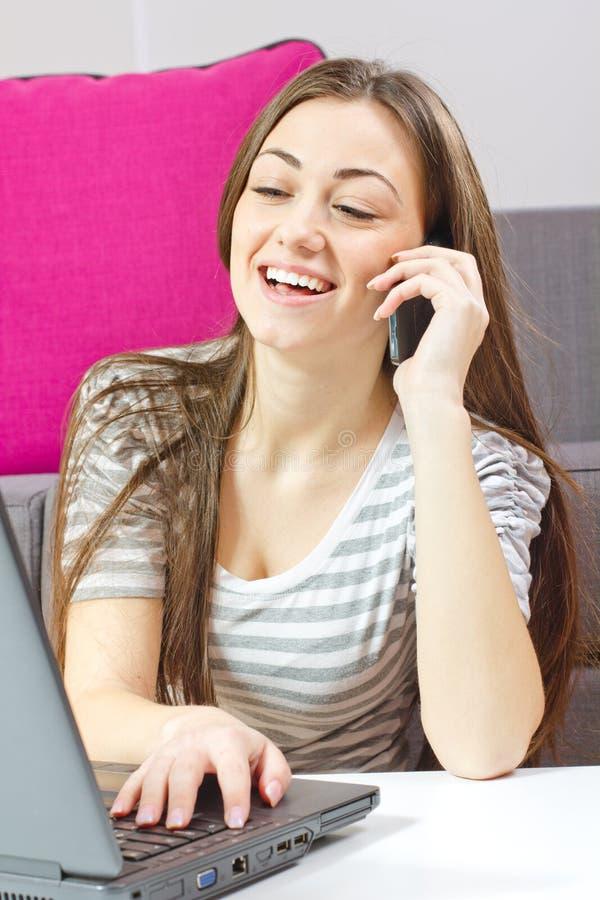 Jonge vrouw die telefonisch spreken en laptop met behulp van stock foto's