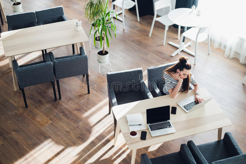 Jonge vrouw die terloops aan haar laptop in een koffie werken Bored aantrekkelijke vrouwelijke zitting met een kop van koffie op  royalty-vrije stock foto